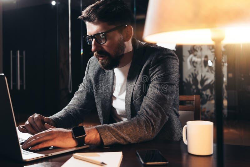 Gebaarde jonge zakenman die in zolderruimte bij nacht werken De medewerker zit door de houten lijst met lamp en bureauhulpmiddele royalty-vrije stock foto