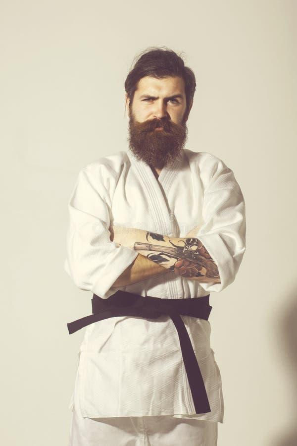 Gebaarde karatemens, brutale Kaukasische ernstige hipster in kimono stock foto's