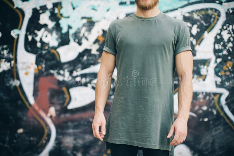 Gebaarde kerel die groene lege t-shirt en zwarte jeans draagt, die zich op de straat bevinden horizontaal stock fotografie