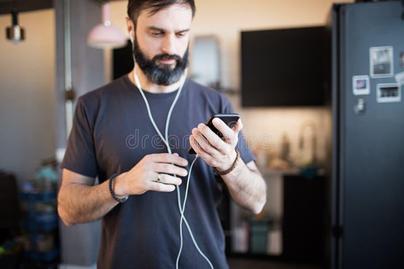 In gebaarde kerel die toevallige grijze t-shirt het luisteren muziek in oortelefoons dragen, die sociale netwerken controleren op stock foto's