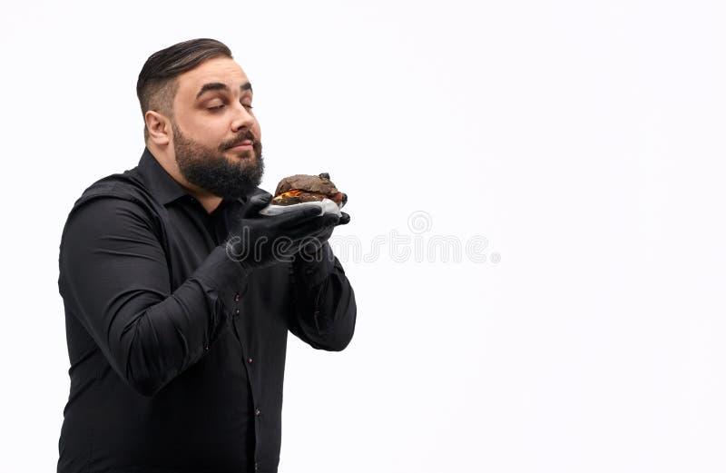 Gebaarde kerel ruikende hamburger stock foto's