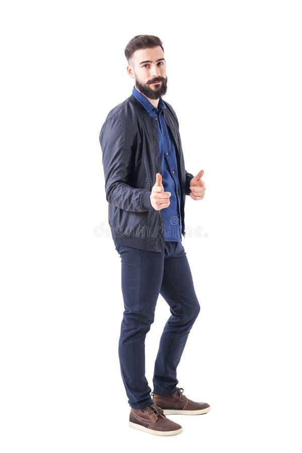 Gebaarde knappe hipster die bommenwerpersjasje dragen die u kiezen en vinger richten op camera stock foto