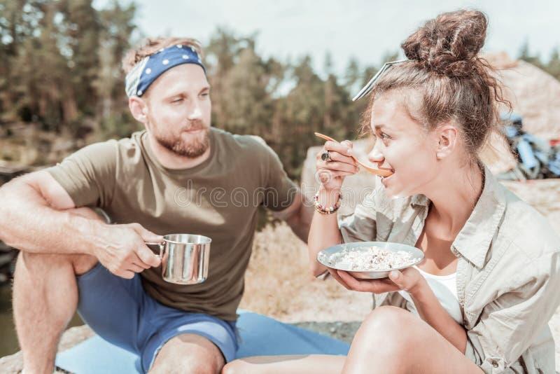 Gebaarde knappe mens die op zijn meisje letten etend terwijl het reizen in bergen royalty-vrije stock foto