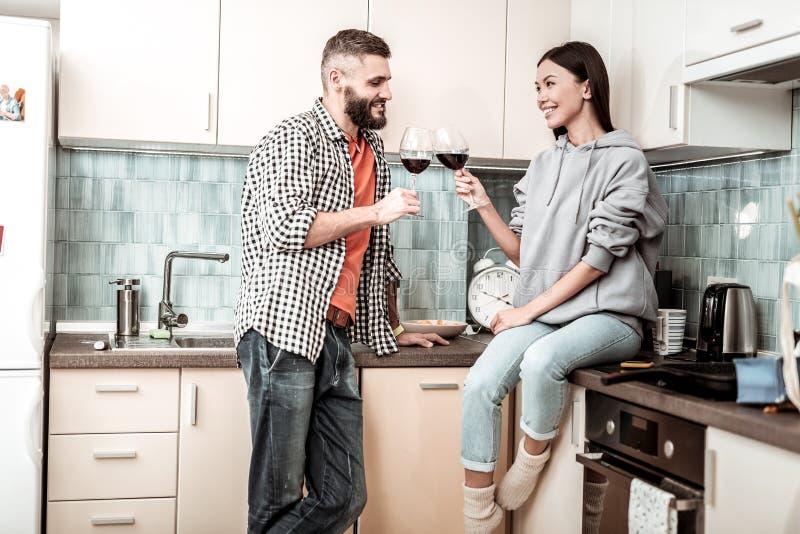 Gebaarde knappe mens het drinken wijn met zijn aantrekkelijk meisje stock afbeeldingen
