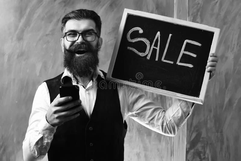 Gebaarde mens, brutale Kaukasische hipster met de verkoopinschrijving van de smartphoneholding stock fotografie