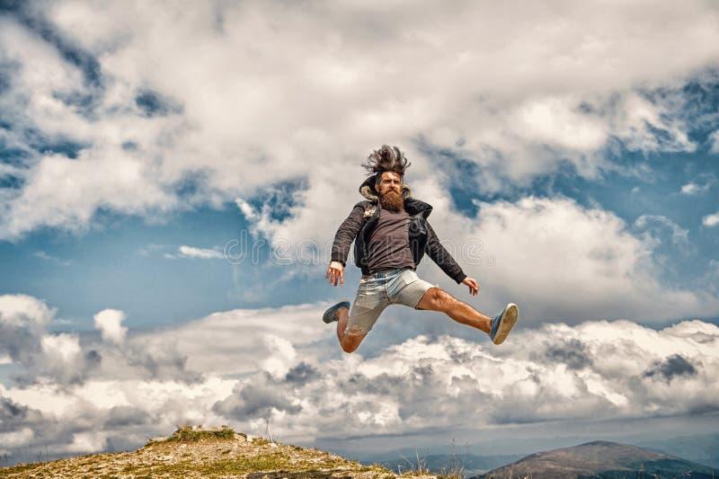 Gebaarde mens, brutale Kaukasische hipster met snorsprong op berg stock fotografie