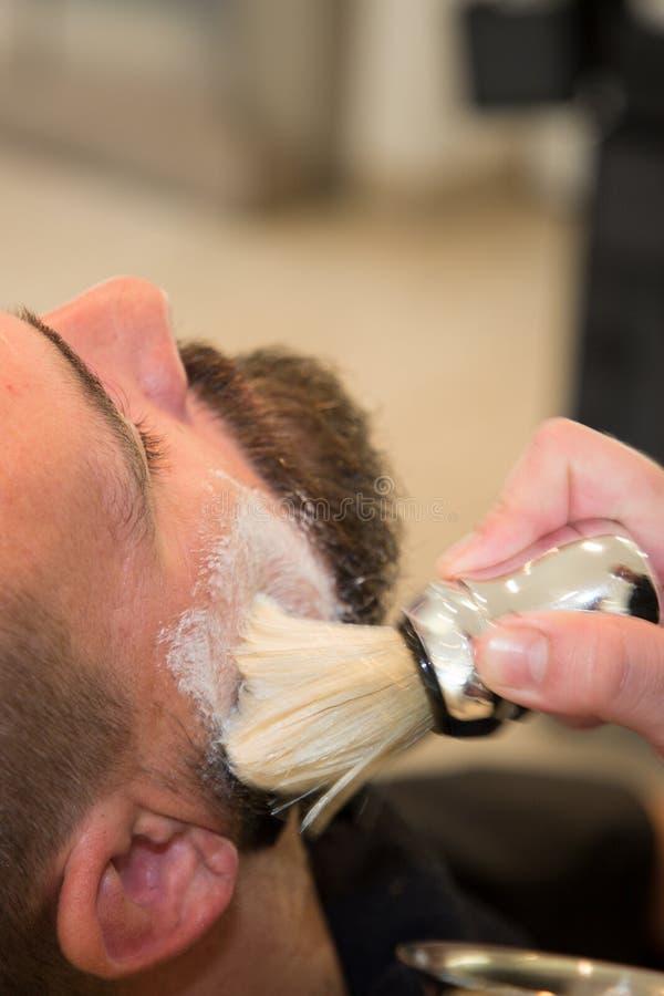 Gebaarde mens die baardkapsel krijgen bij kapper bij herenkapper stock afbeelding