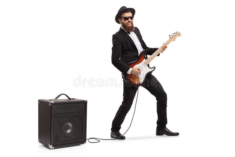 Gebaarde mens die een elektrische gitaar spelen die in een amp?re wordt gestopt stock fotografie