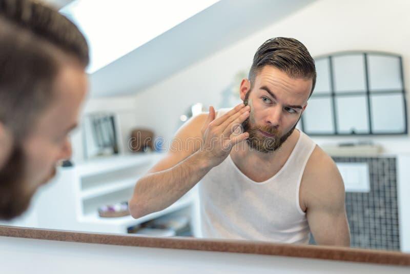 Gebaarde mens die een gezichtsmasker toepassen stock foto's