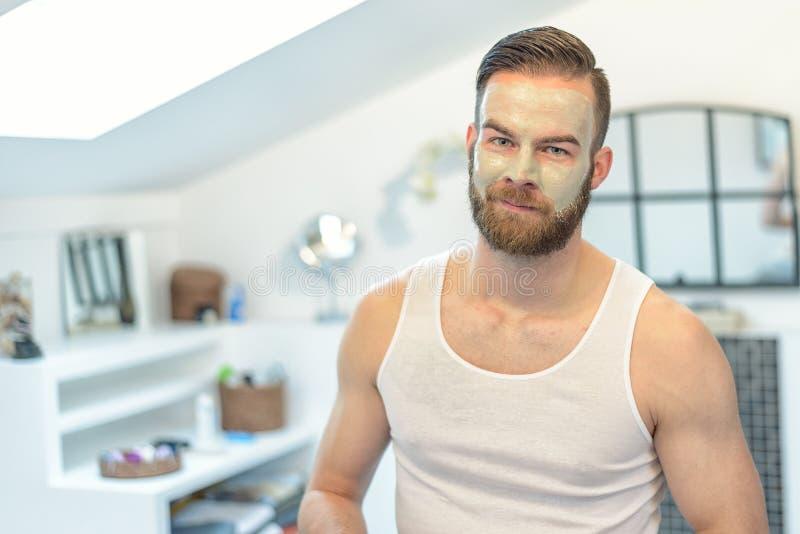 Gebaarde mens die een gezichtsmasker toepassen royalty-vrije stock afbeelding