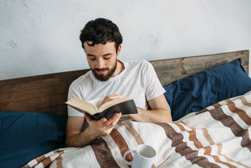 Gebaarde mens die een groot boek lezen die in zijn slaapkamer liggen stock fotografie
