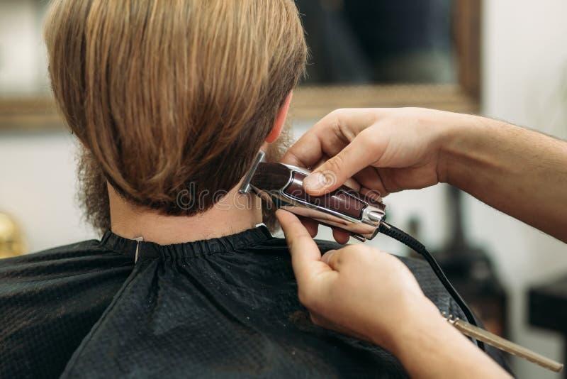 Gebaarde mens die een kapsel met een haarclippers hebben Achter mening stock foto