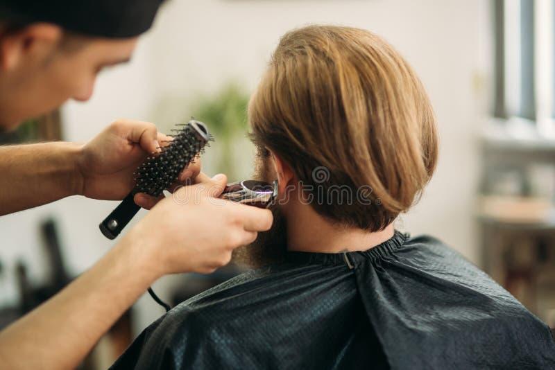 Gebaarde mens die een kapsel met een haarclippers hebben Achter mening stock afbeeldingen