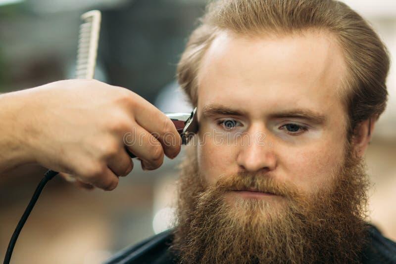 Gebaarde mens die een kapsel met een haarclippers hebben Close-upmening met ondiepe diepte van gebied stock afbeelding