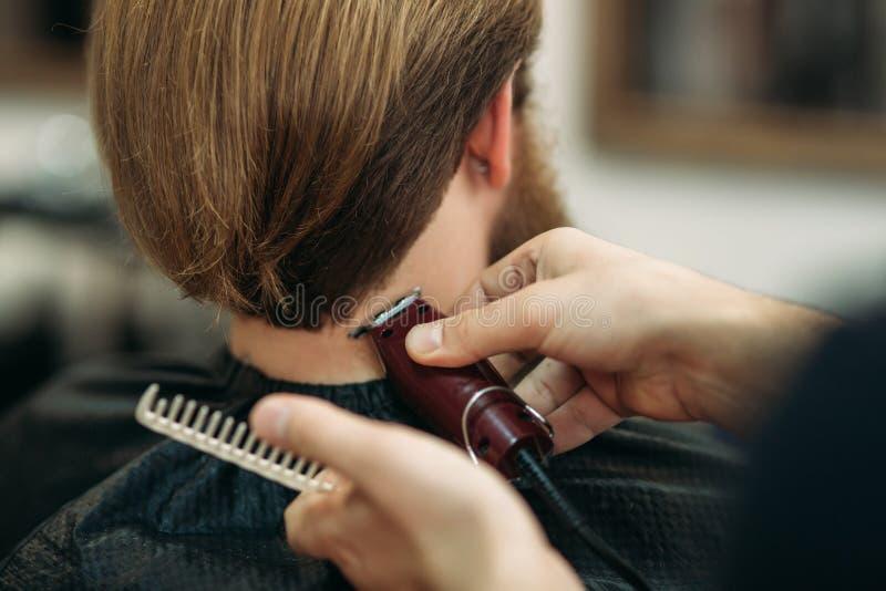 Gebaarde mens die een kapsel met een haarclippers hebben Close-upmening met ondiepe diepte van gebied stock fotografie