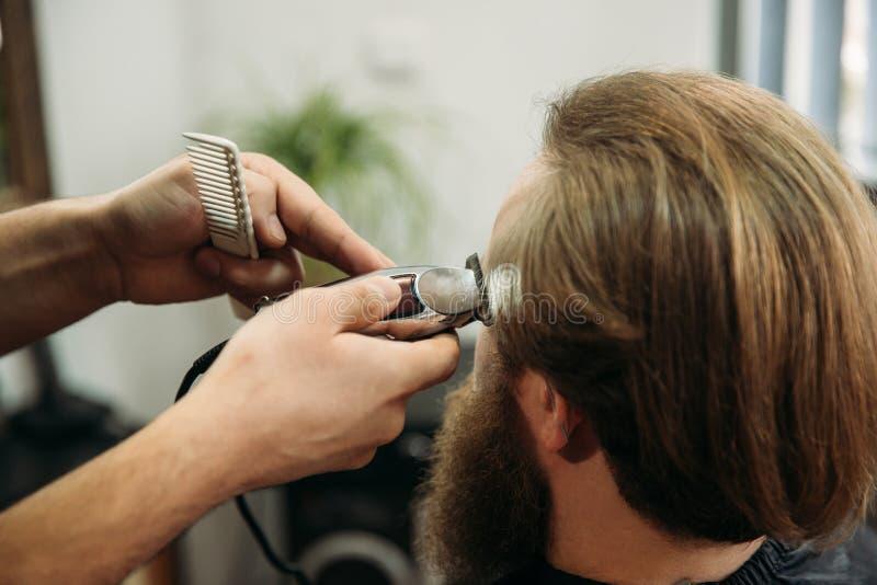 Gebaarde mens die een kapsel met een haarclippers hebben Close-upmening met ondiepe diepte van gebied stock foto's