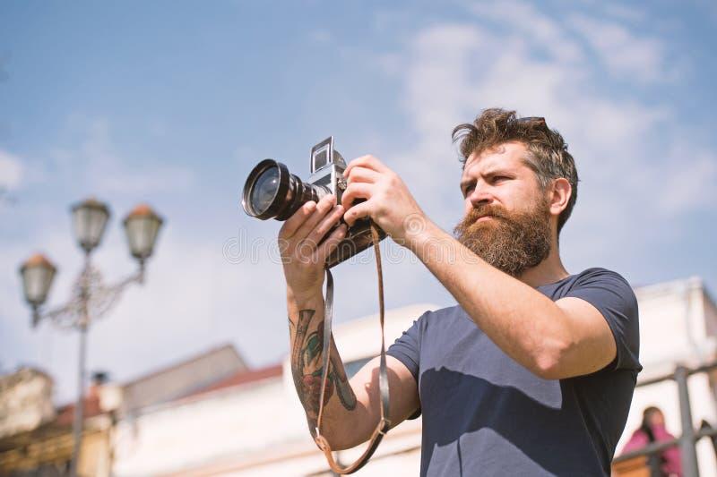 Gebaarde mens die foto op zonnige dag nemen De mens met baard en de snor op geconcentreerd gezicht, hemel op achtergrond, defocus stock fotografie
