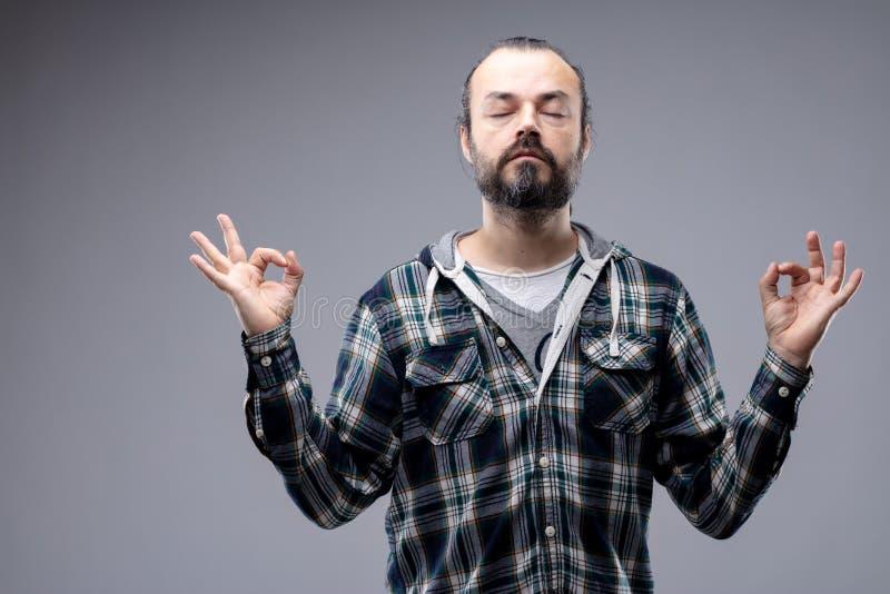 Gebaarde mens die met een rustige uitdrukking mediteren royalty-vrije stock afbeelding