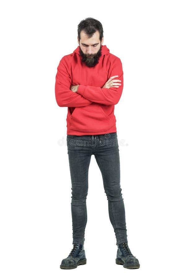 Gebaarde mens die met gekruiste wapens in rood sweatshirt met een kap neer kijken royalty-vrije stock afbeeldingen