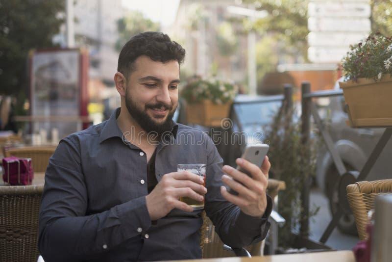 Gebaarde mens die smartphone in barterras terwijl het drinken van bij kijken royalty-vrije stock afbeeldingen