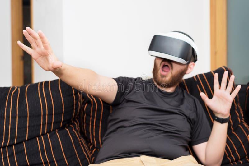 Gebaarde mens die virtuele werkelijkheidsbeschermende brillen dragen stock foto