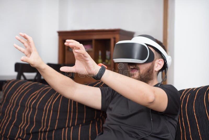 Gebaarde mens die virtuele werkelijkheidsbeschermende brillen dragen stock afbeeldingen