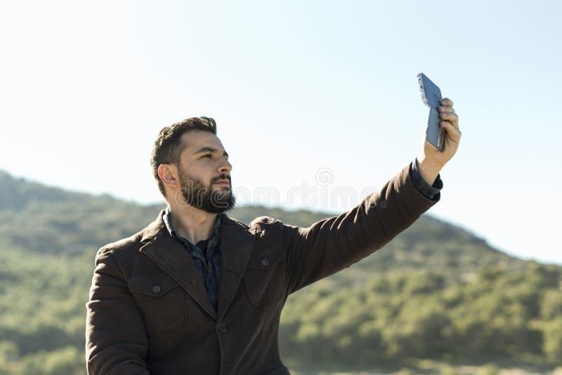 Gebaarde mens die zelfportret nemen stock foto