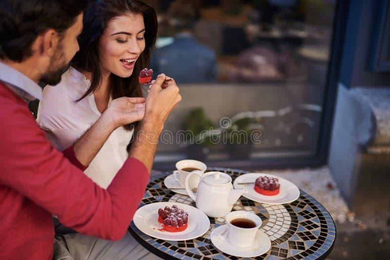 Gebaarde mens die zijn charmant meisje met lepel van smakelijke cake voeden stock afbeelding