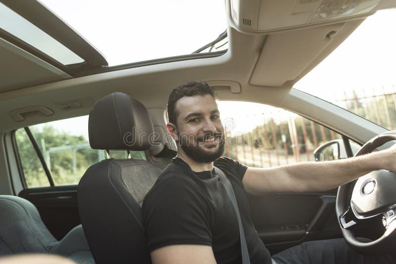 Gebaarde mens die zijn het beeld van de carinzonsondergang het glimlachen drijven stock foto's