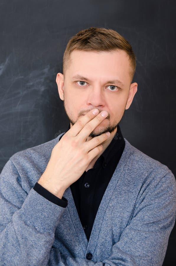 Gebaarde mens die zijn mond behandelen met zijn hand stock afbeeldingen
