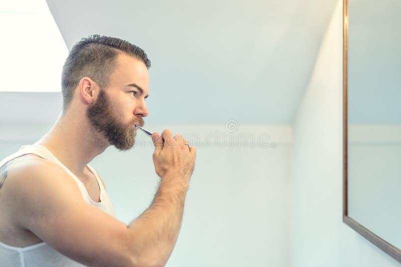 Gebaarde mens die zijn tanden borstelen stock fotografie