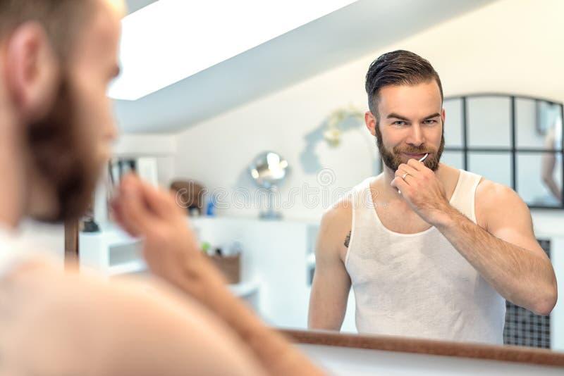 Gebaarde mens die zijn tanden borstelen royalty-vrije stock foto