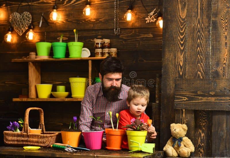 Gebaarde mens en weinig de liefdeaard van het jongenskind Bloemzorg het water geven Grondmeststoffen de gelukkige tuinlieden met  stock afbeeldingen