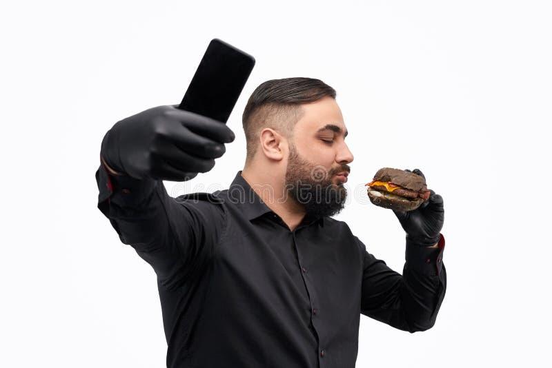 Gebaarde mens het kussen hamburger en het nemen selfie stock foto