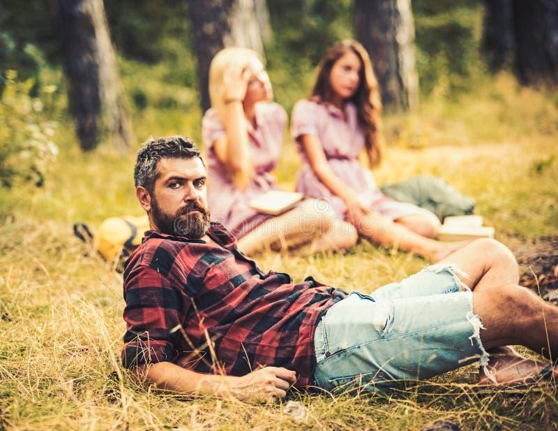 Gebaarde mens in houthakkersoverhemd het besteden tijd met vrienden in openlucht Knappe mens die op glas in hout liggen openlucht stock fotografie