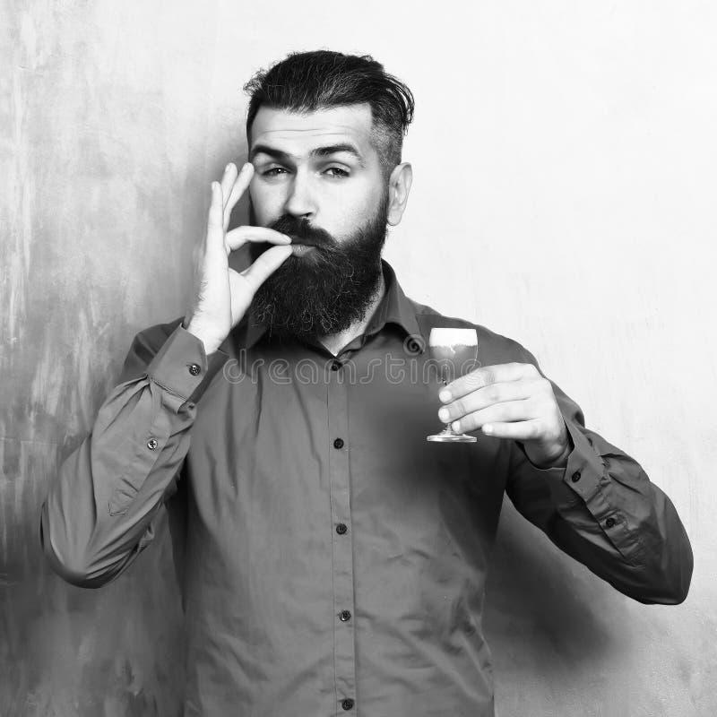 Gebaarde mens, lange baard Brutale Kaukasisch tevreden hipster met snor in bruin overhemd die alcoholisch rood geschoten houden  royalty-vrije stock afbeeldingen