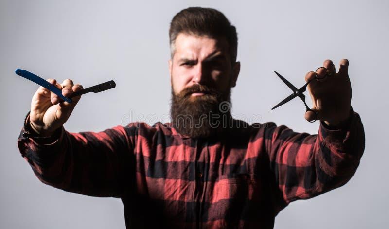 Gebaarde mens, lange baard, brutale, Kaukasische hipster met snor Kappersschaar en recht scheermes, kapperswinkel mannetje stock afbeeldingen