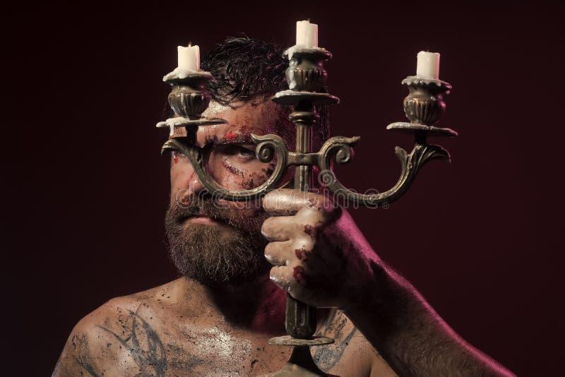 Gebaarde mens met bloedig gezicht, getatoeeerde borst met kaarsenhouder stock afbeelding