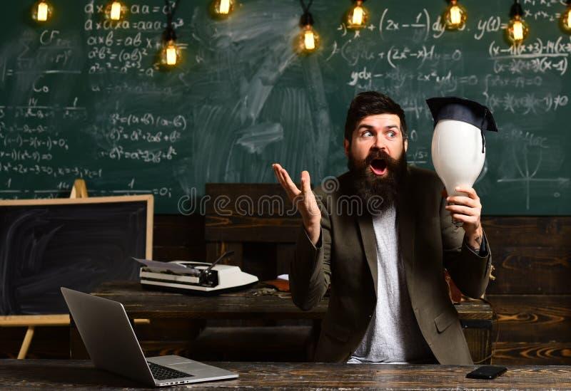 Gebaarde mens met bol geworden idee in klaslokaal Gebaarde wetenschapper met lightbulb op bord, verlichting royalty-vrije stock afbeelding