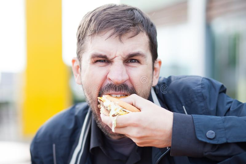 Gebaarde mens met een eetlust die een hamburger op de straat eten stock fotografie