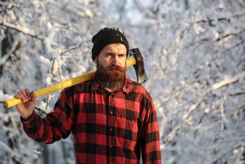 Gebaarde mens met een houthakkersbijl, bosbouw Knappe mens, hipster in sneeuw boshouthakker in het hout met een bijl  royalty-vrije stock afbeeldingen