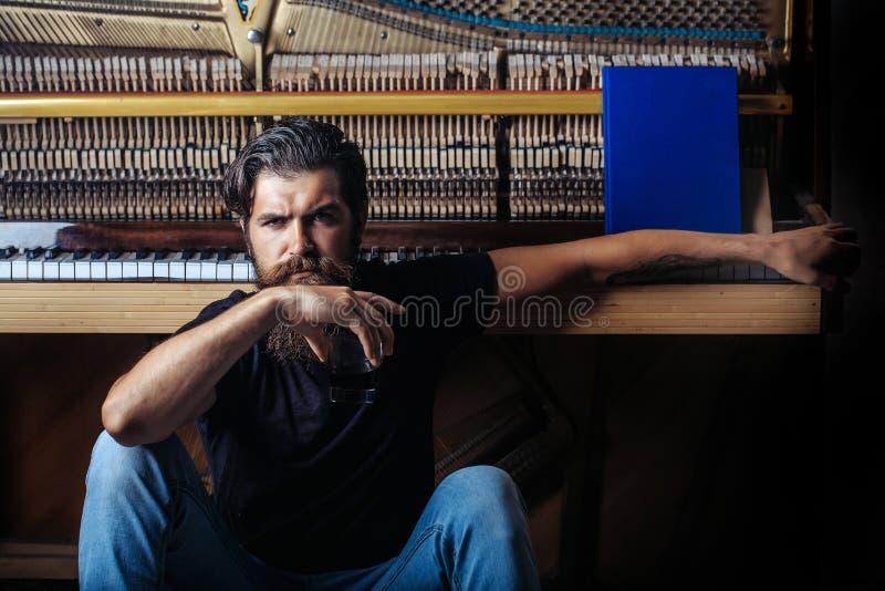 Gebaarde mens met glas dichtbij houten piano royalty-vrije stock fotografie