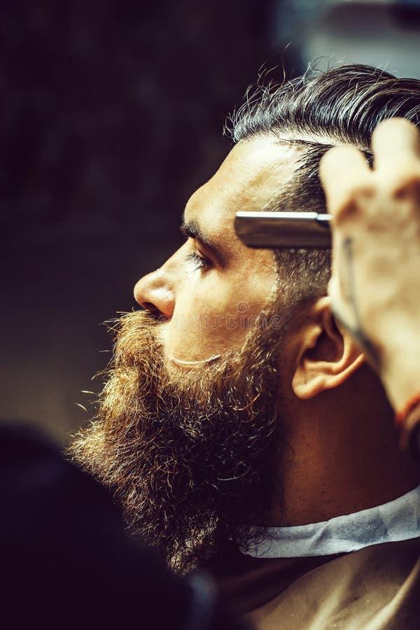 Gebaarde mens met lange baard die haar het scheren met scheermes krijgen stock afbeelding