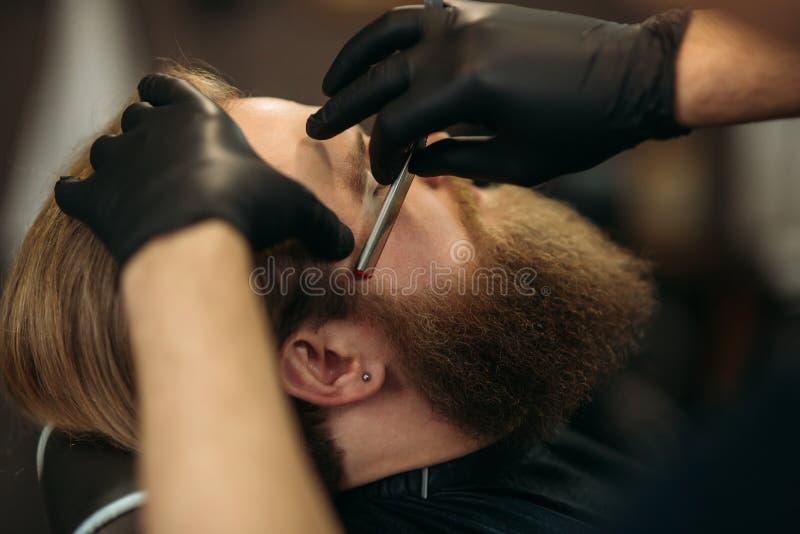 Gebaarde mens met lange baard die het modieuze haar scheren, kapsel, met scheermes krijgen door kapper in herenkapper royalty-vrije stock afbeelding