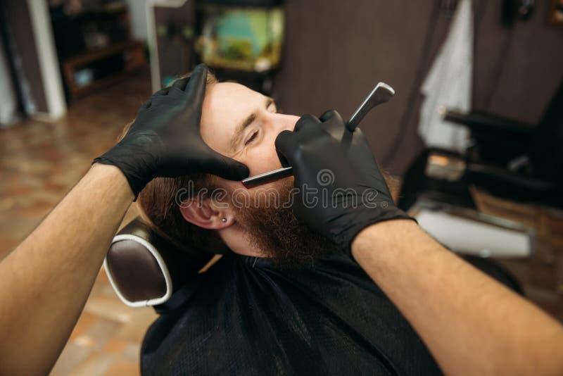 Gebaarde mens met lange baard die het modieuze haar scheren, kapsel, met scheermes krijgen door kapper in herenkapper royalty-vrije stock foto