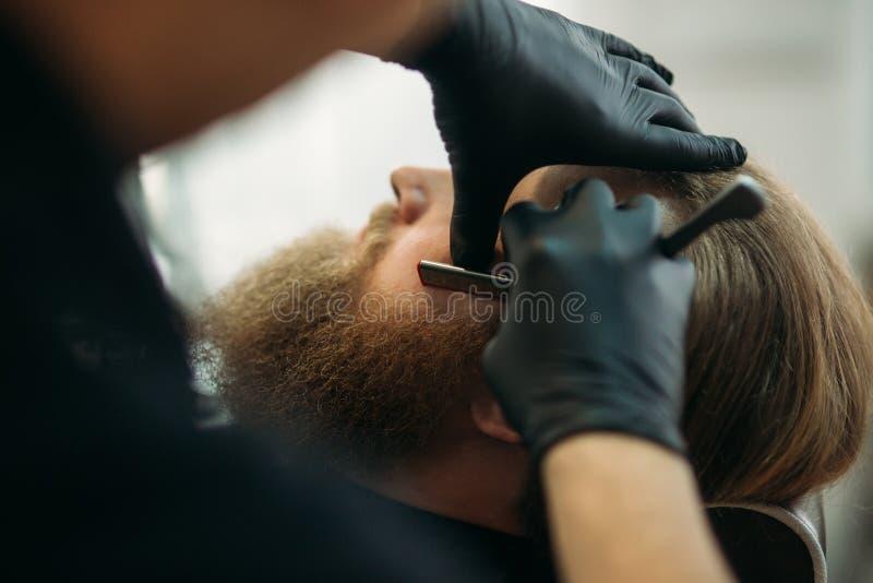 Gebaarde mens met lange baard die het modieuze haar scheren, kapsel, met scheermes krijgen door kapper in herenkapper stock foto