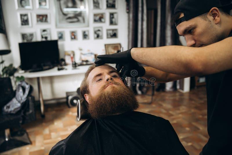 Gebaarde mens met lange baard die het modieuze haar scheren, kapsel, met scheermes krijgen door kapper in herenkapper stock afbeelding