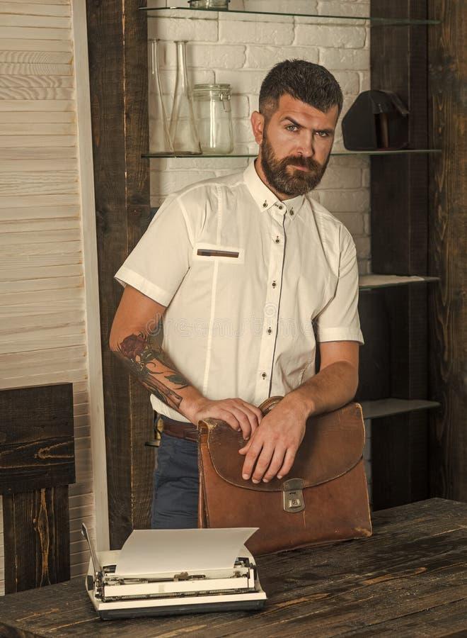 Gebaarde mens met uitstekende aktentas en schrijfmachine bij bureau royalty-vrije stock fotografie