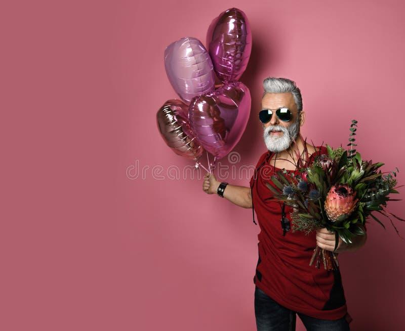 Gebaarde mens op middelbare leeftijd met ballons en bloemen stock foto