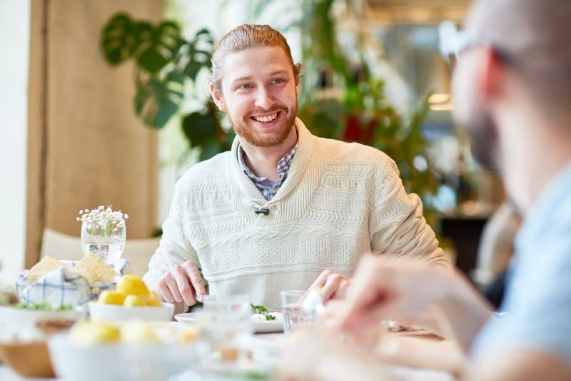 Gebaarde mens in sweaterzitting met vrienden in koffie stock foto